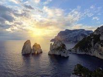 Rocas de Faraglioni que se elevan para arriba de las aguas mediterráneas azules brillantes en la isla de Capri, Italia imagen de archivo