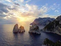 Rocas de Faraglioni que se elevan para arriba de las aguas mediterráneas azules brillantes en la isla de Capri, Italia foto de archivo libre de regalías