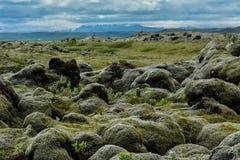 Rocas de la lava cubiertas por el musgo con el cielo azul y las montañas en los vagos fotos de archivo