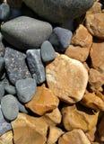Rocas de la oscuridad y del moreno en una playa fotografía de archivo