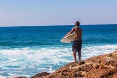 Rocas de la persona que practica surf que saltan el mar de la entrada Imágenes de archivo libres de regalías