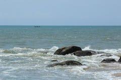 Rocas de la playa con un barco de los pescados Fotos de archivo