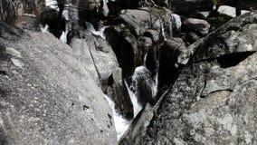 Rocas del granito con agua que conecta en cascada abajo del parque California de Yosemite almacen de video