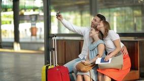 Rocas del tiempo de vacaciones Familia hermosa sonriente que toma Selfie con Smartphone mientras que espera su vuelo en el aeropu almacen de video