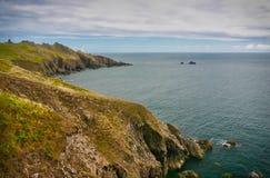 Rocas delante del faro del punto del comienzo en la playa con los acantilados, Devon, Inglaterra imagen de archivo