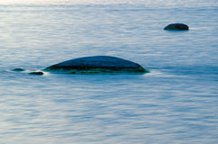 Rocas en agua azul suave Imagen de archivo