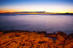 Rocas en el mar brumoso en puesta del sol Imagen de archivo libre de regalías