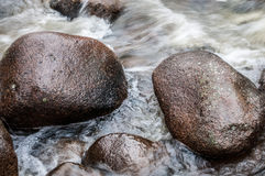 Rocas en el río de la agua corriente Fotos de archivo