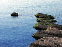 Rocas en fila en el mar Imagen de archivo