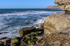 Rocas en la costa con las ondas que se estrellan, con el acantilado en el fondo, playa de Oporto Barril, Ericeira - Mafra, Portug imagen de archivo