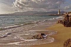 Rocas en la playa con las ondas, estatua y cielo dramático, vista de la ciudad de Palma y montañas, Palma, Mallorca, España imagen de archivo libre de regalías