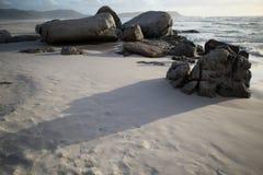 Rocas en la playa en la puesta del sol imagenes de archivo
