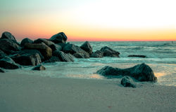 Rocas en la puesta del sol en la bahía Foto de archivo