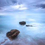 Rocas en olas oceánicas debajo del cielo nublado. Mún tiempo. Fotografía de archivo