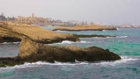 Rocas en ondas y costa con la fortaleza Ribat en la ciudad de Monastir, Túnez almacen de video