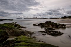 Rocas en una playa cerca del cabo Reinga en la oscuridad, isla del norte, Nueva Zelanda imagen de archivo libre de regalías