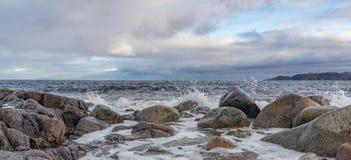 Rocas grandes en la orilla del mar de Barents contra la perspectiva de un cielo tempestuoso oscuro Fotografía de archivo libre de regalías