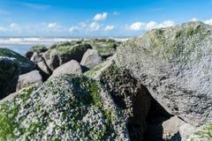 Rocas grandes en la playa con el cielo azul imagenes de archivo