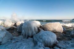 Rocas heladas por un lago en invierno fotos de archivo