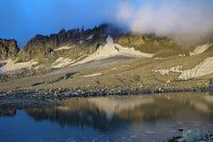 Rocas iluminadas por el sol naciente y el pequeño lago de la moraine en el Ca Imagen de archivo