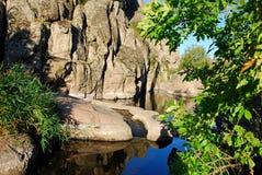 Rocas inaccesibles, colgando sobre el agua Entre los árboles sombríos Fotos de archivo libres de regalías