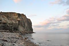 Rocas por el Mar Negro en puesta del sol imagen de archivo