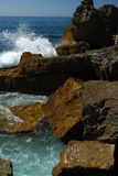 Rocas por el océano imagenes de archivo