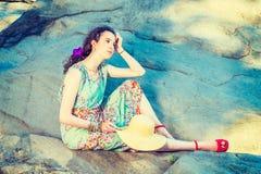 Rocas que se sientan de la mujer americana joven en el Central Park, Nueva York, con referencia a Imagenes de archivo