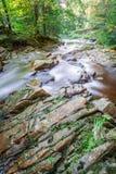 Rocas resbaladizas en una corriente de la montaña Foto de archivo libre de regalías
