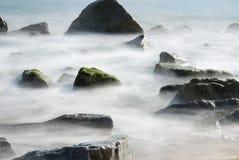 Rocas sobre la playa del agua de Badalona - España foto de archivo