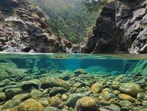 Rocas sobre y debajo del agua en un río imagen de archivo libre de regalías