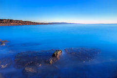 Rocas sumergidas, océano azul, cielo claro en puesta del sol de la playa de la bahía Imagen de archivo