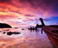 Rocas sumergidas y barco de la cola larga en la puesta del sol Foto de archivo libre de regalías