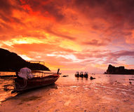 Rocas sumergidas y barco de la cola larga en la puesta del sol Fotos de archivo