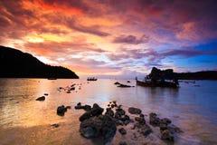 Rocas sumergidas y barco de la cola larga en la puesta del sol Imagenes de archivo