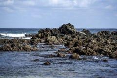Rocas volcánicas que resaltan de la evaluación en la costa del th Imagenes de archivo