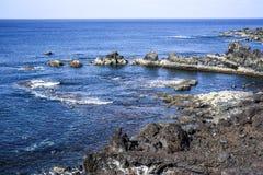 Rocas volcánicas que resaltan de la evaluación en la costa del th Foto de archivo