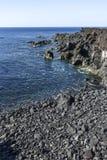 Rocas volcánicas que resaltan de la evaluación en la costa del th Fotos de archivo