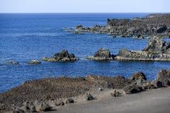 Rocas volcánicas que resaltan de la evaluación en la costa del th Foto de archivo libre de regalías