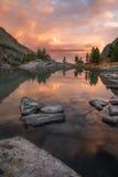 Rocas y árboles que reflejan en aguas rosadas del lago mountain de la puesta del sol, naturaleza Autumn Landscape de la montaña d Fotos de archivo libres de regalías