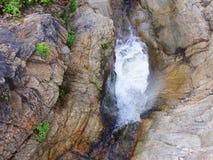 Rocas y acantilados costeros, pequeño puente de California sobre una cascada de conexión en cascada con salpicar el agua - carret Imagenes de archivo