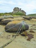 Rocas y cuerdas del amarre en la playa Imagen de archivo