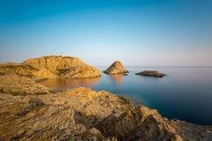 Rocas y faro rojos de Ile Rousse en Córcega Imagen de archivo libre de regalías