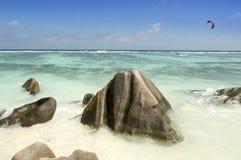 Rocas y hombre de los cantos rodados que hacen el kitesurf en la playa d'Argent de la fuente de Anse, isla de Digue del La, Seych Fotografía de archivo