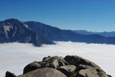 Rocas y Sierra Nevada sobre las nubes Fotos de archivo