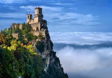 Rocca della Guaita, the most ancient fortress of San Marino, Italy. The fog at the bottom creates the illusion of clouds stock photography