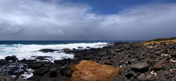 Rocce arancio e nere sul puntello dell'oceano fotografia stock libera da diritti