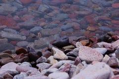 Rocce attraverso chiara acqua fotografia stock