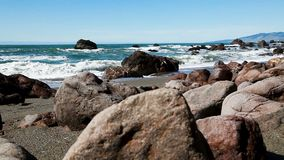 Rocce basse dell'angolazione di ripresa sulla spiaggia con le onde di oceano video d archivio
