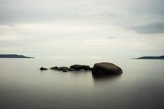 Rocce calme del lago con i colori freddi Fotografia Stock